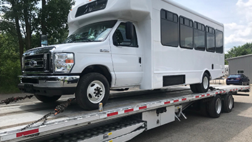 2018 Ford E-450 Shuttle Bus hauled on a step deck trailer