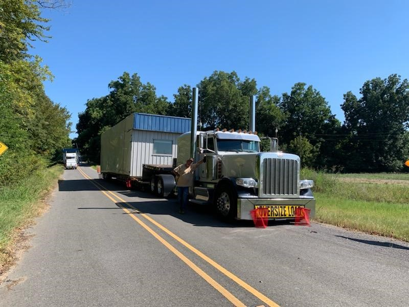 Semi trucks driving with mobile offices on trailers