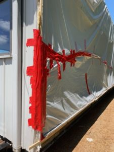 Tarp fully repaired with red tape.