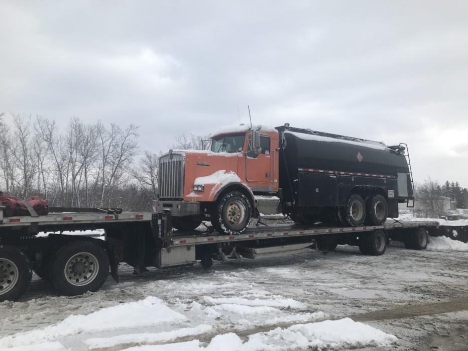 Kenworth Heavy Duty Truck transported on an RGN in snow.