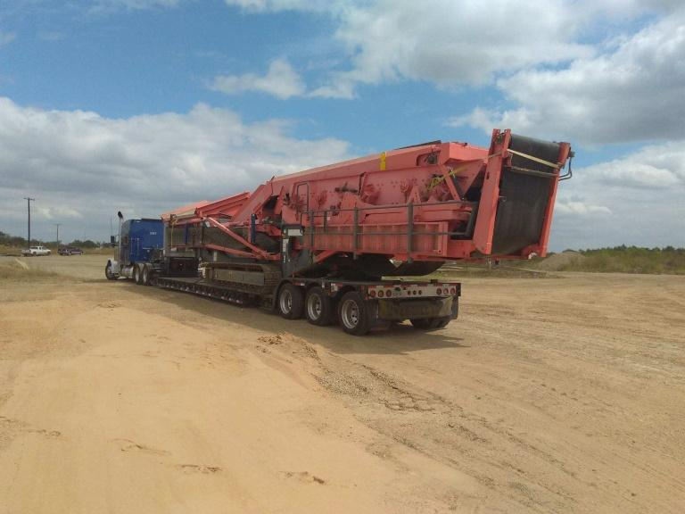 Rough terrain crane being driven off on an RGN trailer