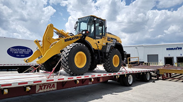 Komatsu wheel loader shipped on a flatbed trailer