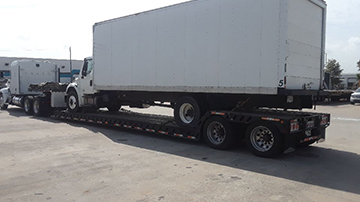 2014 Freightliner M2 box truck being moved with an RGN Trailer