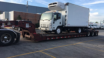 2011 Isuzu Box Truck shipped on an RGN Trailer