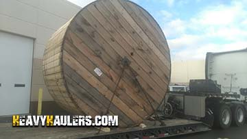 A reel of cable in transport on a rgn trailer