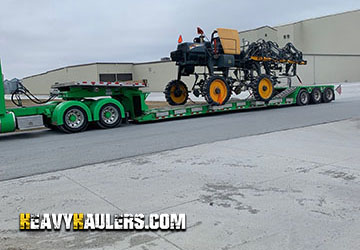 John Deere transported on trailer with outriggers