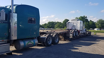 Peterbilt sleeper truck transported on an RGN trailer