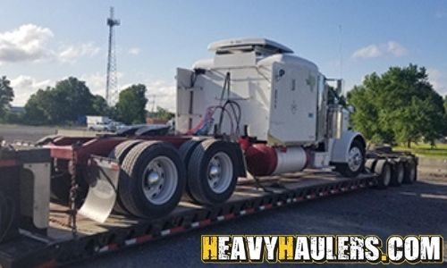 Peterbilt sleeper truck transported on an RGN trailer