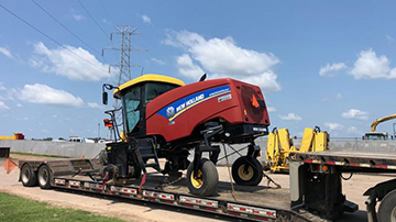 2015 New Holland Swather Speedrower transported on an RGN trailer