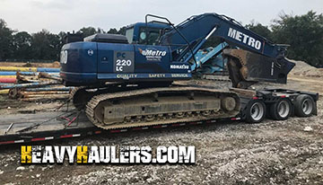 Heavy Komatsu excavator loaded on an RGN