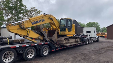 Komatsu PC228 excavator transported on an RGN trailer