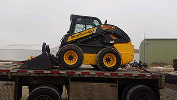 Hauling a New Holland L230 skid steer
