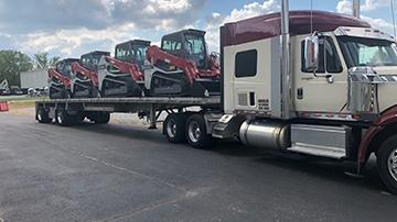 Takeuchi TL10V2 track loader transported to South Dakota on a flatbed trailer