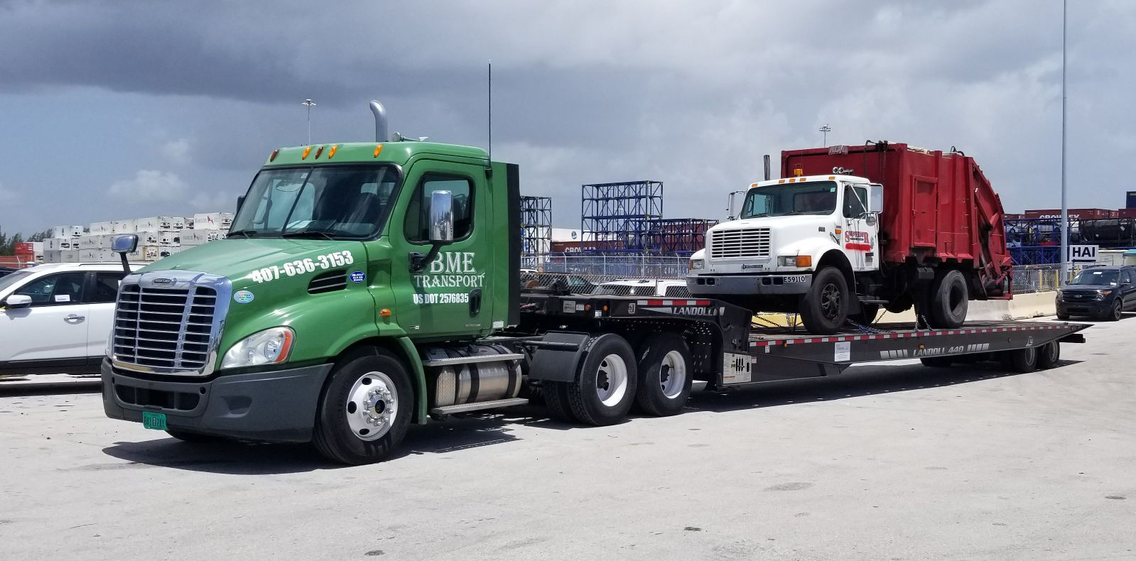 A 2003 international 4900 garbage truck loaded on a step-deck trailer