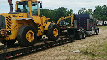 Volvo l60e wheel loader transported on an RGN Trailer