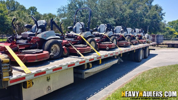 lawn mowers being transported on a trailer